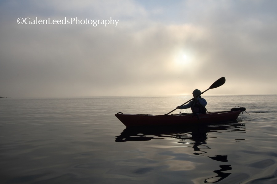 The brightest light source is behind, under, and around the kayaker, turning them into the essence of kayaking, by removing the individuality and fine details, that sails through a sea of light